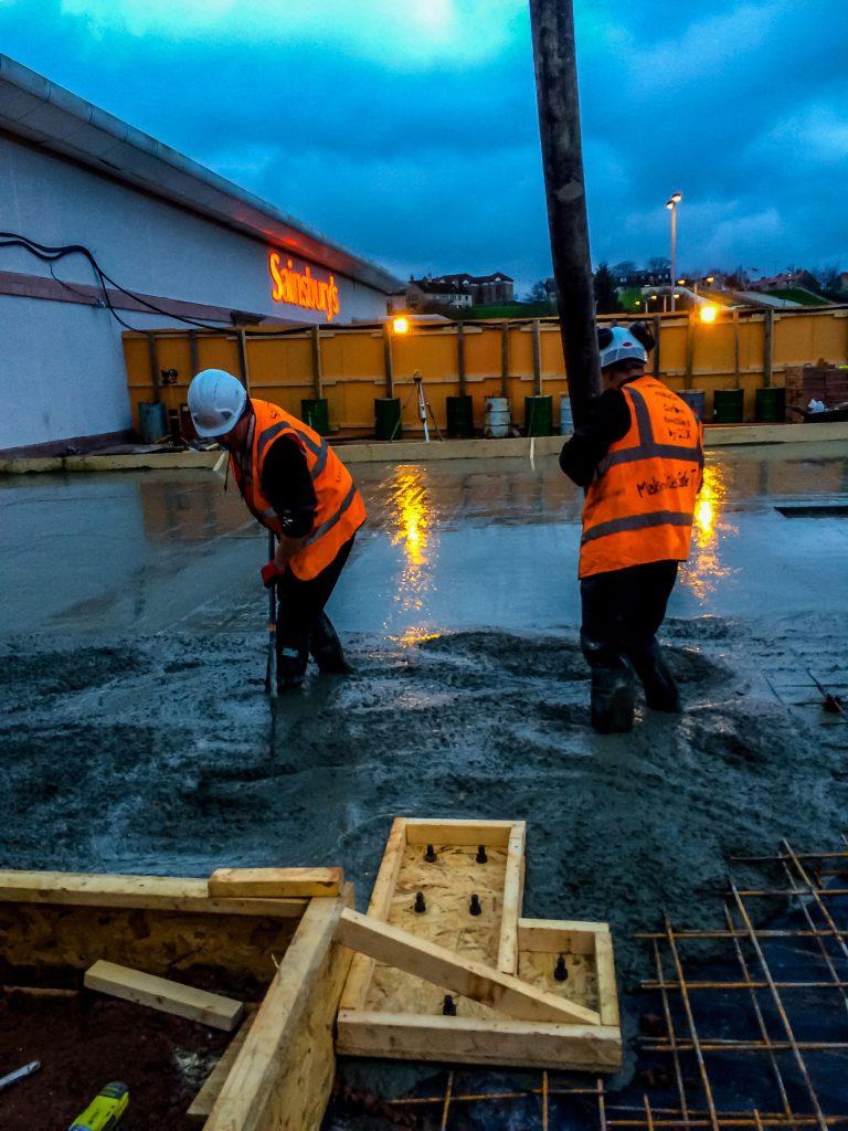 2 men working on laying concrete